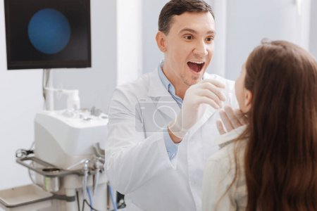 Delighted ENT doctor examining sore throat