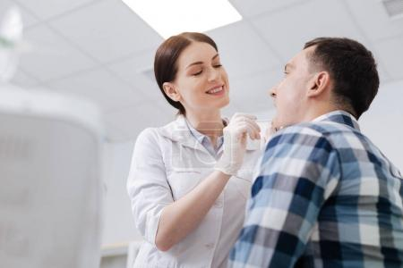 Smiling doctor examining sore throat