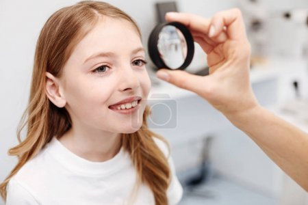 Excellent scrupulous ophthalmologist performing a checkup