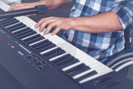 Young disabled man playing musical keyboard in the studio