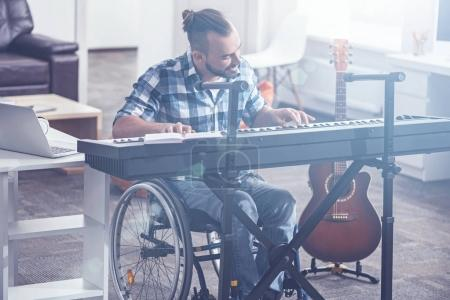 Inspired man in the wheelchair playing musical instrument indoors