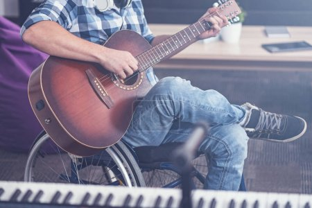 Young disabled man enjoying playing guitar in the studio