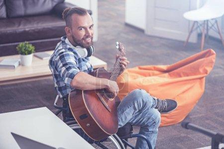 Homme joyeux sur fauteuil roulant, jouer de la guitare dans le studio d'enregistrement sonore