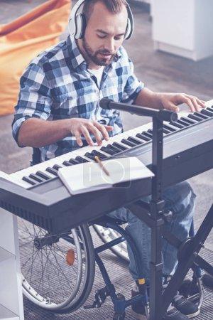 Enthousiaste désactivé jouant des instruments de musique dans le studio d'enregistrement