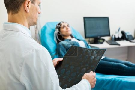 Doctor looking through CT results while conducting electroencephalography