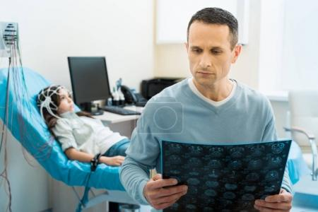 Father examining CT results of his daughter