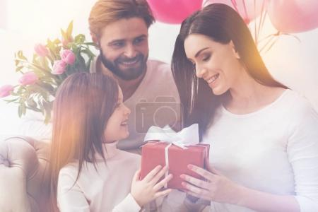 Charming cute girl giving her mom a present