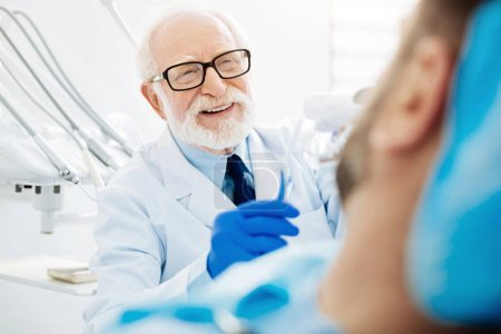 Close up of experienced dentist with false teeth in hand