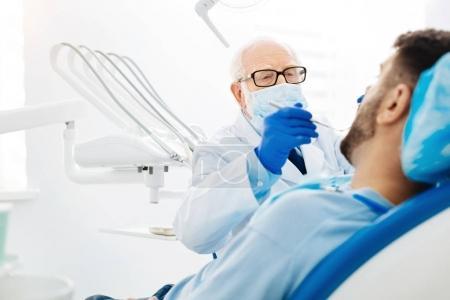 Skilled stomatologist using dental instruments