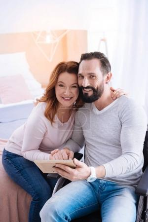 Glad woman and paralyzed man hugging