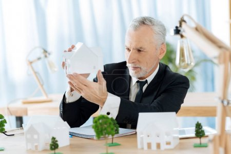 Reliable real estate agent looking at the miniature of a house and thinking