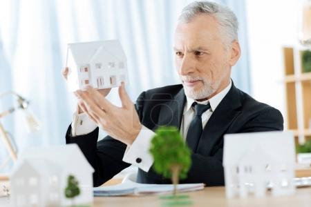 Smiling real estate agent holding a miniature of a house while working