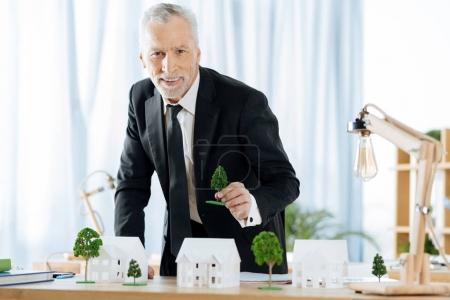 Positive employee waiting for the visitors in a real estate agency