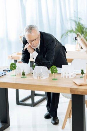 Concentrated experienced realtor looking at the miniature houses and thinking