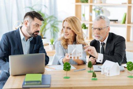 Photo pour Discussion importante. Smart expérimentés qualifiés agences immobilières recherche concentrée assis ensemble dans leur bureau avec une petite miniature - image libre de droit