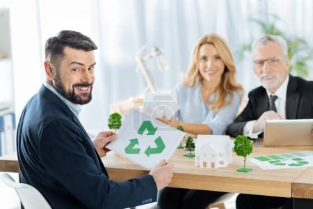 Happy man holding a recycling symbol while sitting with his colleagues