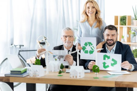 Positive engineers encouraging people to recycling while holding special symbols