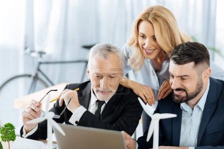 Photo pour Ingénieurs ingénieux. Puce gaie enthousiaste ingénieurs inspiration soient assis ensemble dans leur bureau confortable et en regardant l'écran de leur ordinateur portable - image libre de droit