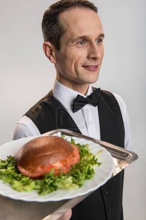 Concentrated attractive male waiter presenting order