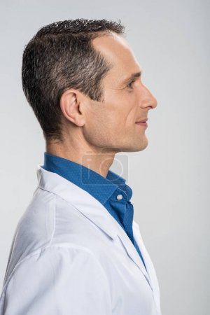 Photo for Doctor in profile. Satisfied professional male doctor posing in profile while grinning  and gazing straight - Royalty Free Image