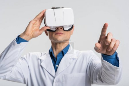 Ambitious male doctor studying patients chart in VR glasses