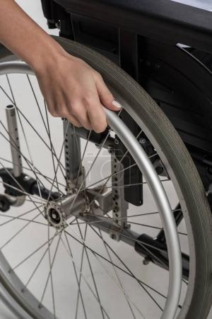 Close up of female hand placing on the wheelchair wheel