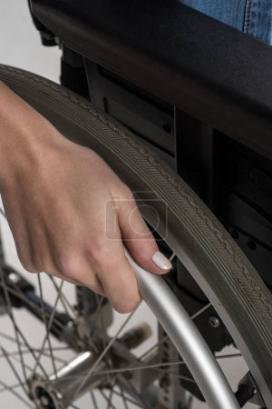Close up of female hand put on the wheelchair wheel