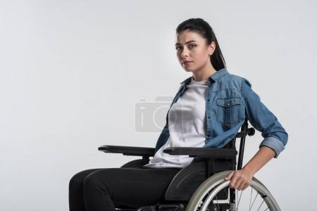 Pensive crippled woman touching wheelchair
