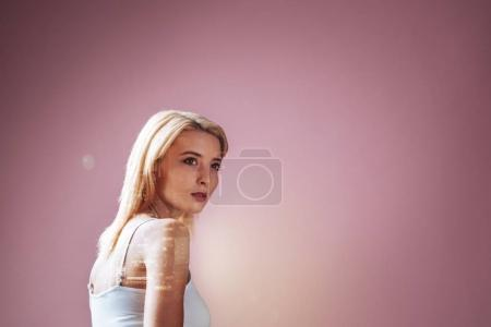 Nice young woman standing against pink wall and looking in front of her while searching for creative ideas