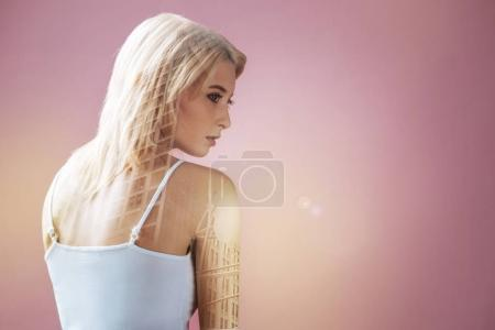 Pleasant pensive young woman turning her head and looking in front of her while having creative thoughts