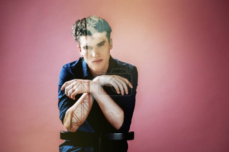 Serious pleasant handsome man sitting on the chair and looking front of him while being thoughtful