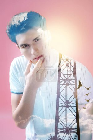 Pleasant thoughtful man looking at the electric wires and holding his chin