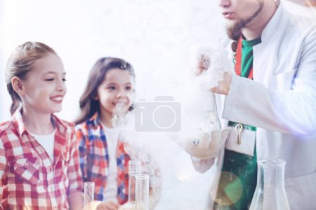 Radiant schoolgirls looking at fuming flask held by chemistry teacher