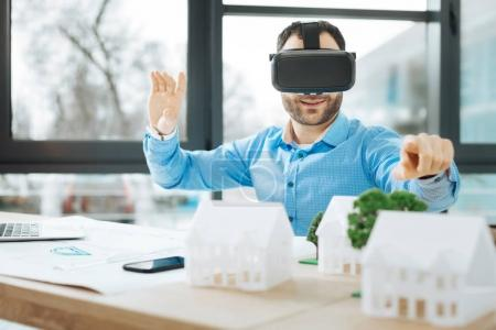 Handsome architect wearing VR headset and pointing at house models