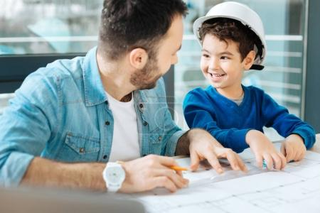 Cute boy helping his father to draw a blueprint