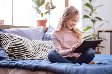 Inspired girl using sitting on the bed with her tablet