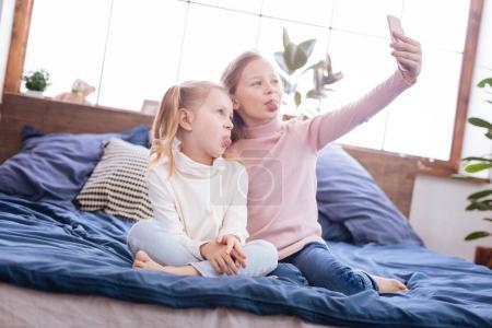 Photo pour Je rigole. Belles sœurs blondes énergiques souriantes et prenant des photos sur leur téléphone et mettant leurs langues sur le lit - image libre de droit