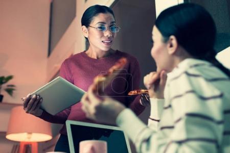 Pleasant women sharing gossips during break at work