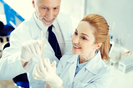 Mature researchers beaming while looking at sample