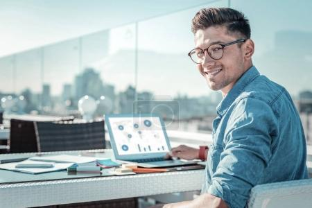 Cheerful college guy beaming while doing homework