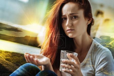 Photo pour Femme frustrée. Fatigué jeune femme malade regardant bouleversé tout en étant assis avec un verre d'eau et tenant les pilules nécessaires dans sa main - image libre de droit
