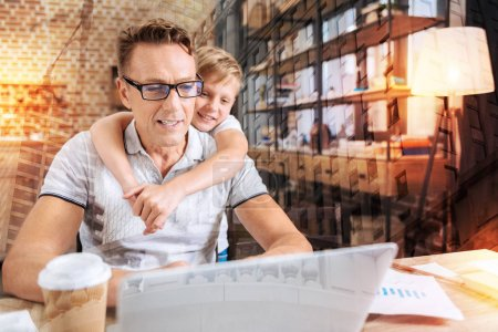 Attentive man looking at the screen while his son standing behind him