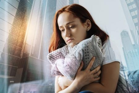 Sad redhead woman looking down and hugging the pillow.