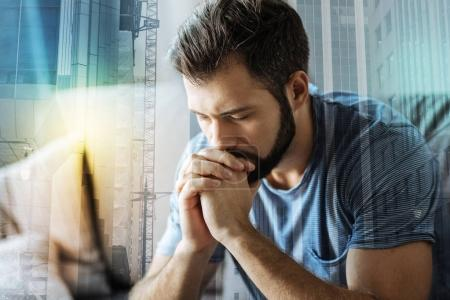 Serious concentrated man closing eyes and holding hands near mouth.
