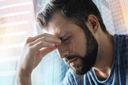 Sick disappointed man feeling bad himself and closing eyes.