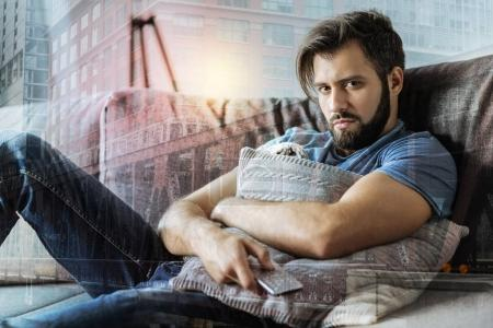 Deep exhausted man hugging the pillow and looking straight.