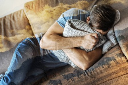 Frustrated depressed man lying and hiding by the pillow.