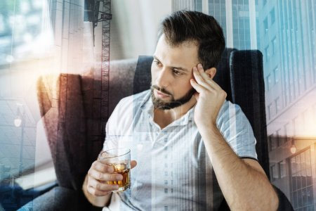 Tired young man sitting in his armchair and drinking alcohol