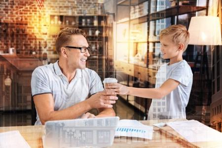 Photo pour Je vous remercie. Gai garçon attentif gentil regardant son père occupé et souriant tout en lui donnant un verre de café savoureux - image libre de droit