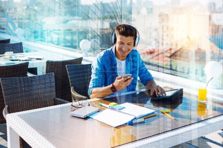 Inspired young man listening to music while working